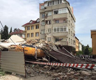 İş makinesi yıkılan binanın altında kaldı
