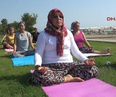 Kadınlar şalvar ve yemeniyle sahilde yoga yapıyor