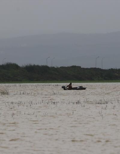 Yağmur sularının altında kalan tarlasını kayıkla gezdi
