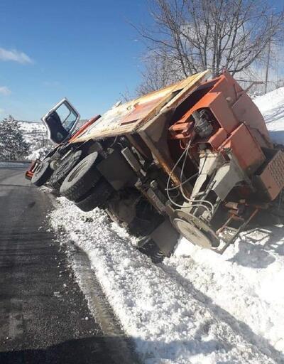 Karla kaplı yolda tuzlama çalışması yapan iş makinesi devrildi