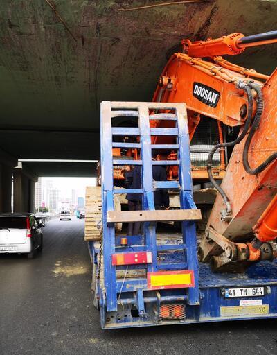 Kartal'da iş makinesi taşıyan TIR köprü altında sıkıştı