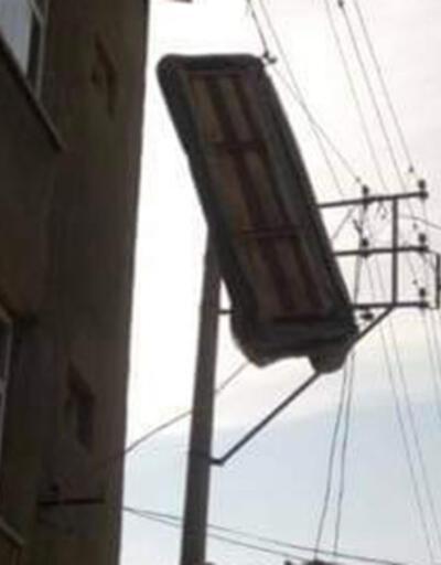 Çatı katından atılan üçlü koltuk, elektrik teline takıldı