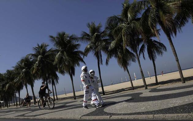 Astronot kıyafeti giyen yaşlı çift, sahilde dolaştı