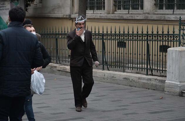 Kamerayı görünce maskeyi indirip poz verdi