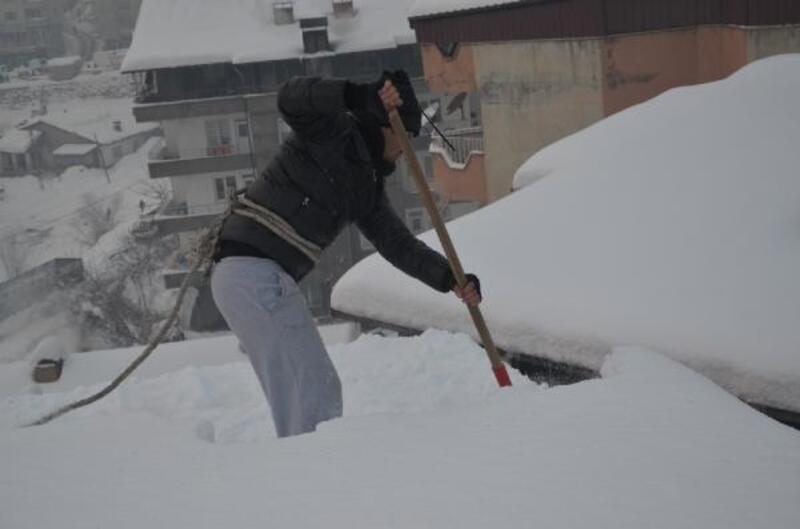 Bellerine halat bağlayıp, çatıları kardan temizliyorlar
