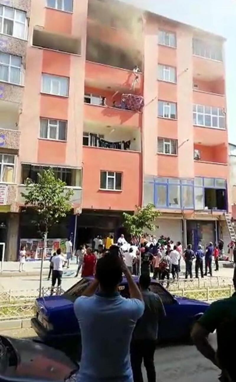 Yangında çocuklarını alt kattaki komşusunun balkonuna sarkıtarakkurtardı