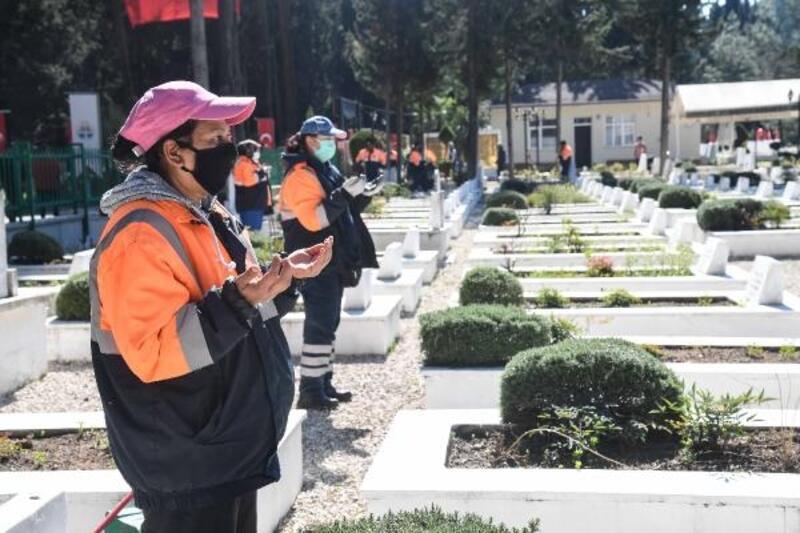 Mezarlıklarda temizlik yapan işçiler, şehitlikteki çalışmalarının ardından dua okudu