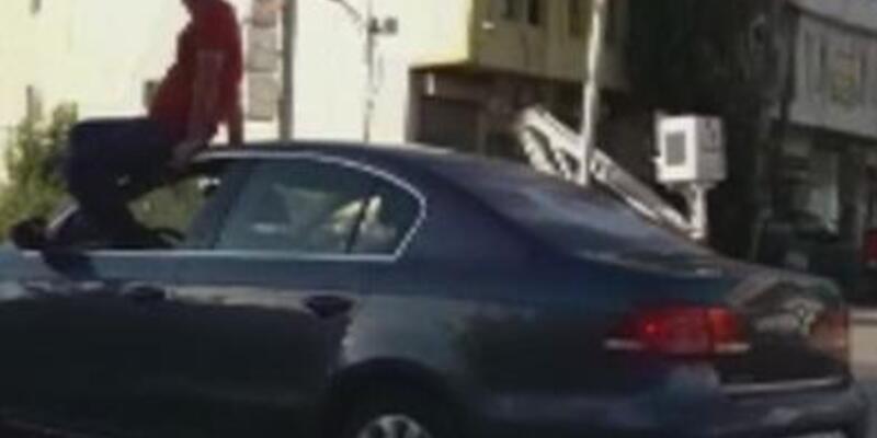 Otomobilin tavanına oturup, direksiyonu ayağıyla kontrol eden sürücüye para cezası