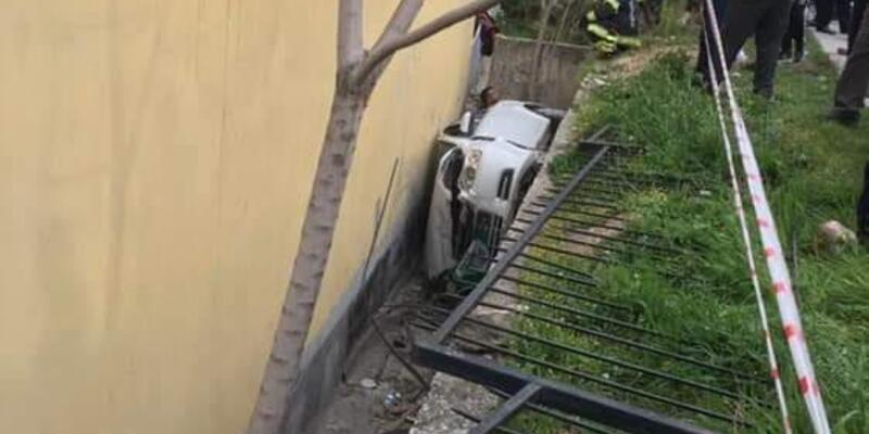 Otomobil ev ile bahçe duvarı arasına yan yatarak devrildi