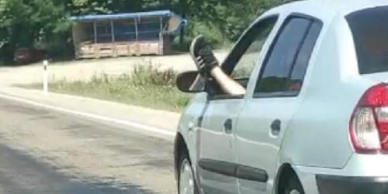 Otomobili, ayağını camdan sarkıtarak kullandı
